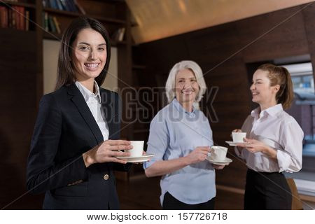 We are friends. Female friendly delighted colleagues smiling while having coffee break and relaxing after work in an office.