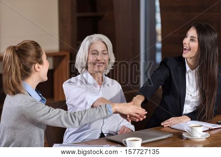 We are the one. Delighted female friendly colleagues holding each others hands while sitting together in an office and smiling.