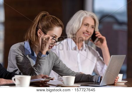 Stay always connected. Female delighted concentrated colleagues using laptop and talking on a cellphone while working together.