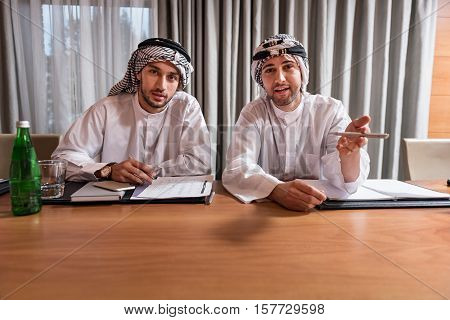 Felling happiness. Two positive delighted attractive men in white robe and keffiyeh on the head sitting at the table discussing and noting some points in the conference hall