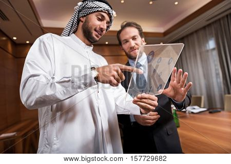 Look here. Young positive Arab man wearing the white robe and keffiyeh on his head standing near the partner and showing him the diagram