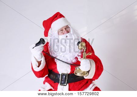 Santa Claus talks to good boys and girls on his telephone while at the North Pole before Christmas Eve. room for your text.