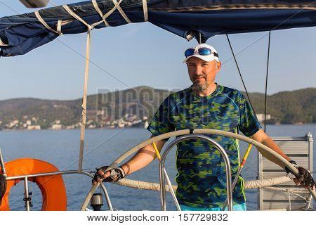 Man skipper steers wheel the sailing yacht boat. Vacation, holidays, travel.