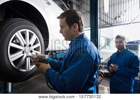 Concentrate on work. Professional experienced car mechanic using pneumatic wrench while chaning car wheel while working in auto service