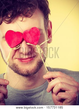 Freedom of feelings. Young happy smiling man with little red hearts on sticks. Romantic man dreaming of his love relationship.