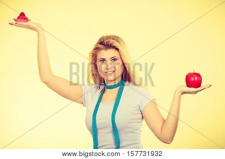 Restrictive diet temptation losing weight concept. Woman choosing between sweet strawberry cupcake and apple having measure tape around her neck. Studio shot on yellow background