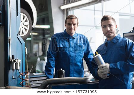 Best service here. Pleasant confident car mechanics standing near car and going to repair it while working in auto service