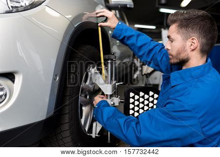 Modern service. Pleasant young mechanic using measure tape and adjusting automobile wheel alignment while working in car station