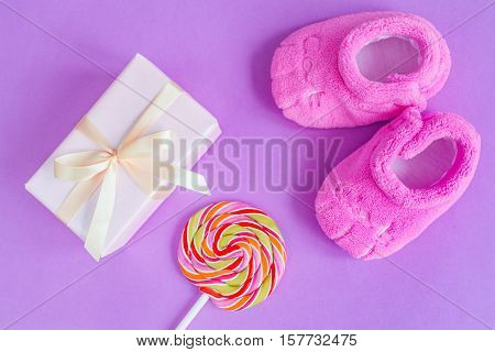baby's bootees and gift box on purple background top view