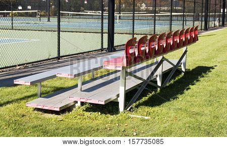 Benches next to tennis courts at a local high school