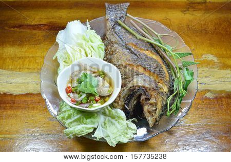 deep fried fish dipping chili fish sauce and vegetable on dish