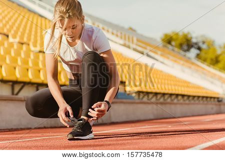 Portrait of a sports woman tie shoelaces at outdoor stadium