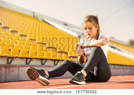 Portrait of a young woman resting and looking on wrist watch at stadium