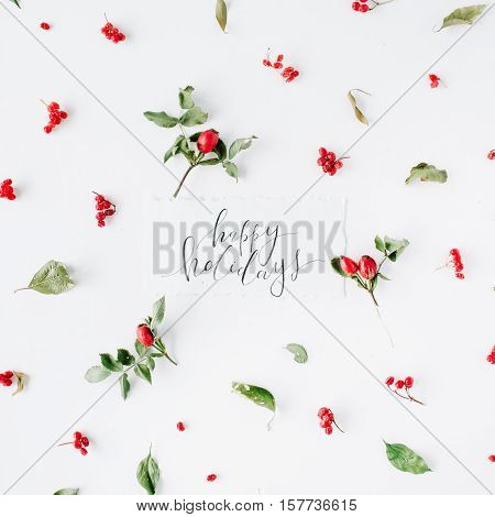 words happy holidays and minimal creative berry arrangement pattern on white. flat lay top view. christmas background wallpaper.