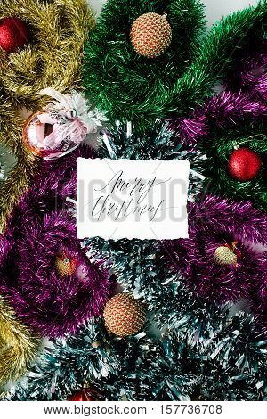 calligraphy words merry christmas and christmas decoration with colored glass balls tinsel toys. flat lay top view