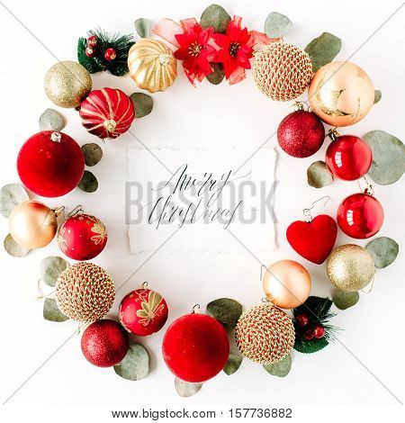 christmas wreath frame made of colored bright christmas balls and calligraphy words merry christmas on white background. flat lay top view