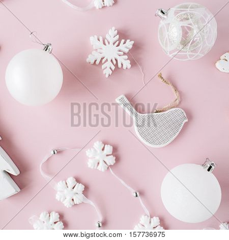 pattern made of white christmas decoration with christmas glass balls tinsel bow elk bird on pink background. christmas wallpaper. flat lay top view