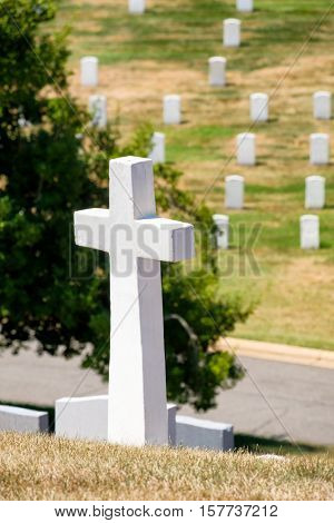 Cross and tombstones on a grassy hill at Arlington National Cemetery near Washington D.C.