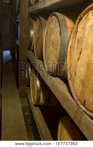 Oak barrels aging on wooden racks inside bourbon distillery Rik house.