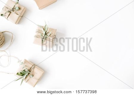 creative arrangement pattern of craft boxes and green branches on white background. flat lay top view