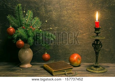 An old brown book with christmas decorations apple and a red candle in bronze candlestick against wooden background