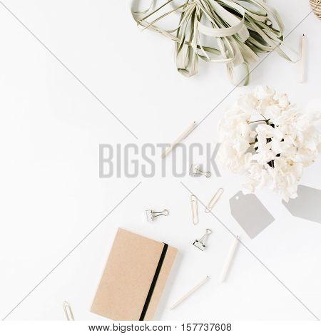 Flat lay top view office table desk. feminine desk workspace with twine pencils floral bouquet craft diary and clips on white background.