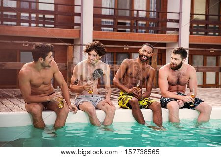 Group of handsome young men sitting and drinking beer near swimming pool