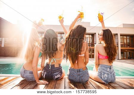 Back view of pretty young women in swimsuit and shorts drinking cocktails near swimming pool