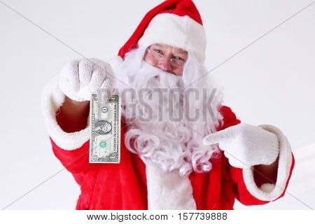 Santa Claus has a ONE DOLLAR BILL just for you. Santa says MERRY CHRISTMAS here have a Buck. Isolated on white with room for your text.