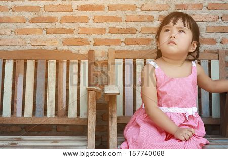 soft focus cute or adorable asian girl children pigtail and wearing pink or red dress lonely sit for relax on the old vintage wood chair with sad feel and looking sky on street and brick wall background