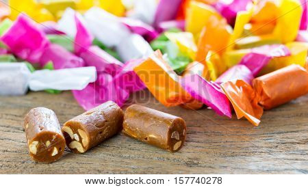 unwrapped sweet candy and blurred colorful wrapped candy on background