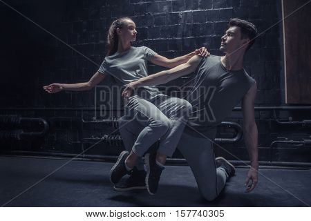 Involved in the process. Involved concentrated young dancer sitting on the leg of other athlete while performing together in the dark lighted room and expressing concentration and confidence