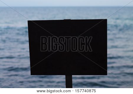 Empty black rectangular sign with sea on the background