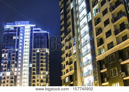 two high-rise buildings at night with illumination