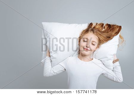 Childish dreams. Positive cute little girl lying on the pillow and smiling while pretending o sleep