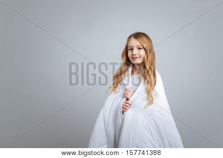 Happ kid. POsitive nice little girl covering with blanket and smiling while standing isolated on grey background