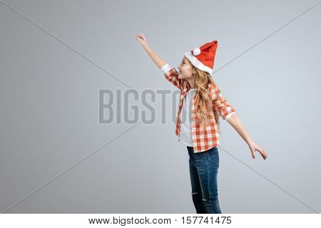 High in the sky. Positive smiling little girl holding hand up and expressing gladness wile standing isolated on grey background