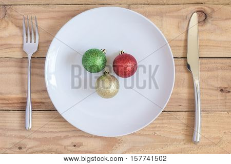 christmas dinner : christmas ball in white dish and fork knife on wood table