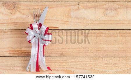 christmas dinner table : decorate silverware with red silver white ribbon on wood. copyspace