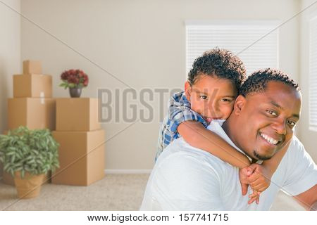 Happy Mixed Race African American Father and Son In Room with Packed Moving Boxes.