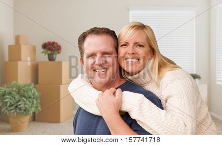 Happy Young Couple in Empty Room with Packed Boxes and Plants.
