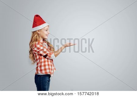 Catch snowflakes. Cheerful young smiling girl wearing hat and catching snowflakes while standing isolated on grey background