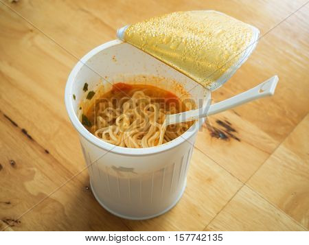 Noodle Cup With A Plastic Fork On Wooden Table