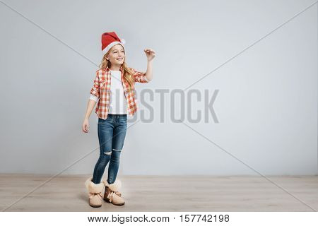 Happy holidays. Cheerful delighted little girl ringing bell and smiling while standing isolated on grey background