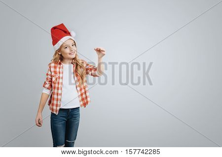 Share positivity. Cheeful smiling little girl holding Christmas bell and smiling while celebrating New Year