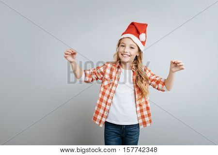 Let it snow. Cheerful delighted little girl smiling and ringing bells while standing islated on rey background