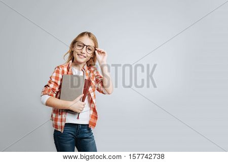 Want to be smart. Cheerful content little girl holding her glasses and keeping books while standing isolated on grey background