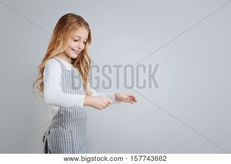 Involved in process. Pleasant pretty little girl cooking and expressing gladness while standing isolated on grey background