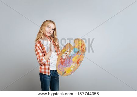 Let me think. Pleasant toughtful little cute girl thinking and holding color palette while thinking out the painting