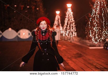 Red-haired girl with red lips in red beret and scarf standing against the background of the Christmas tree. Coloured bokeh. Abstract background. Golden garland. New year's night. Cold evening. Art